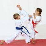 Girl in a kimono hits foot boy in a kimono hits a hand