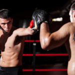 Latin boxer and his coach doing some sparring in the ring